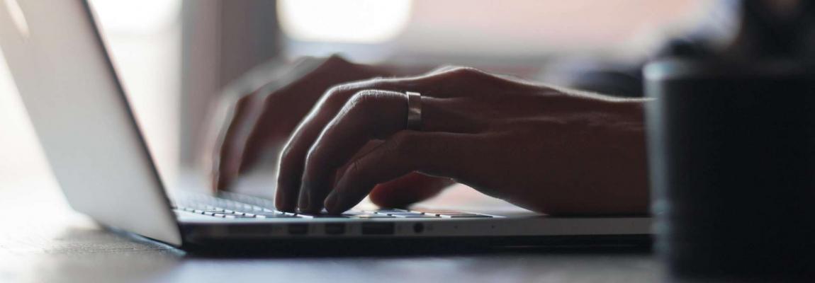 Hände schreiben auf einem Laptop